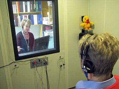 Woman in sound booth for medicaid hearing aids in Cory Land, NY